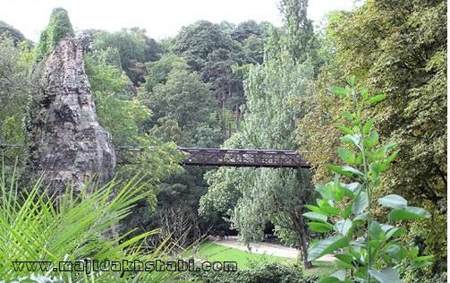 منظره بدیعی از پارک بوت-شومون و پل فلزی که از فراز آن می گذرد در منطقه ۱۹ شهر پاریس